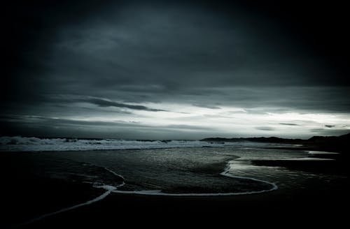 Grayscale Photo of Ocean Under Cloudy Sky