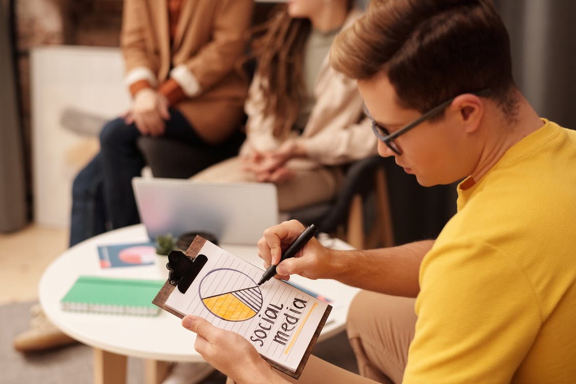 Man in Yellow T-shirt Holding Black Pen Writing on White Paper