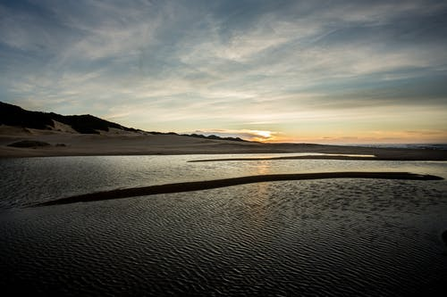 Sandy rough coast washed by tranquil rippling water of lake under cloudy sky in sunset