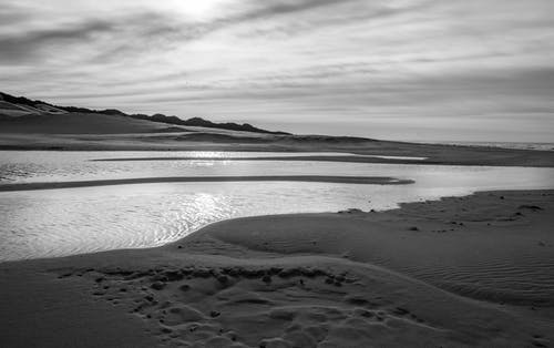 Black and white of endless desert with rippling calm water of pond under cloudy sky