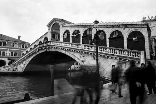 Grayscale Photo of People Walking Near the Bridge