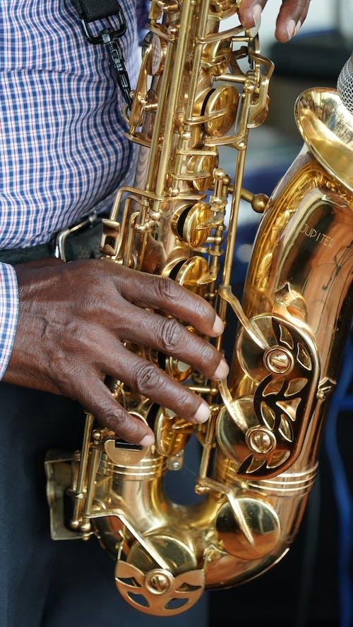 Man in Plaid Dress Shirt Playing Saxophone