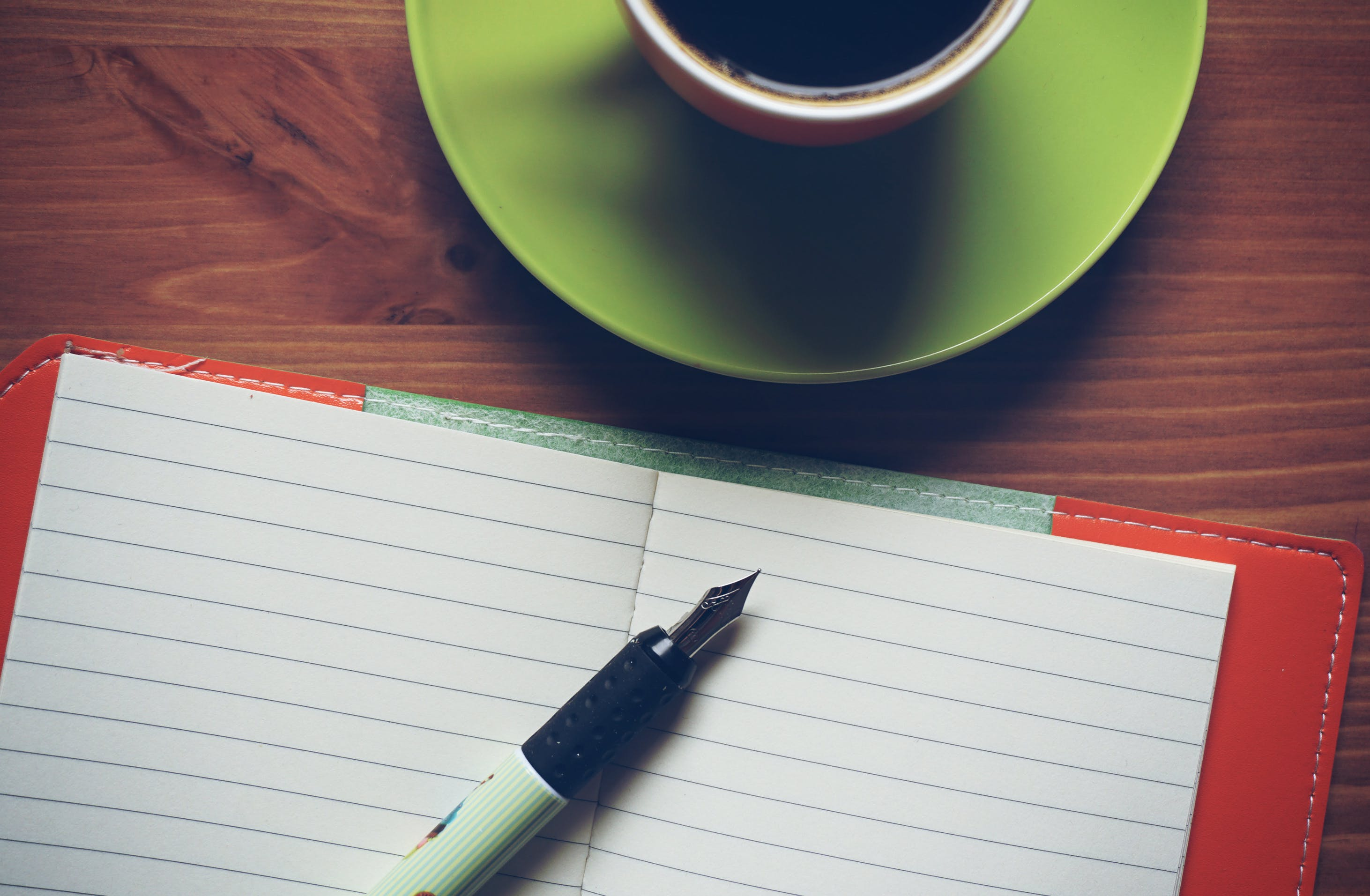 Fountain Pen on Top of Notebook Beside Drinking Mug
