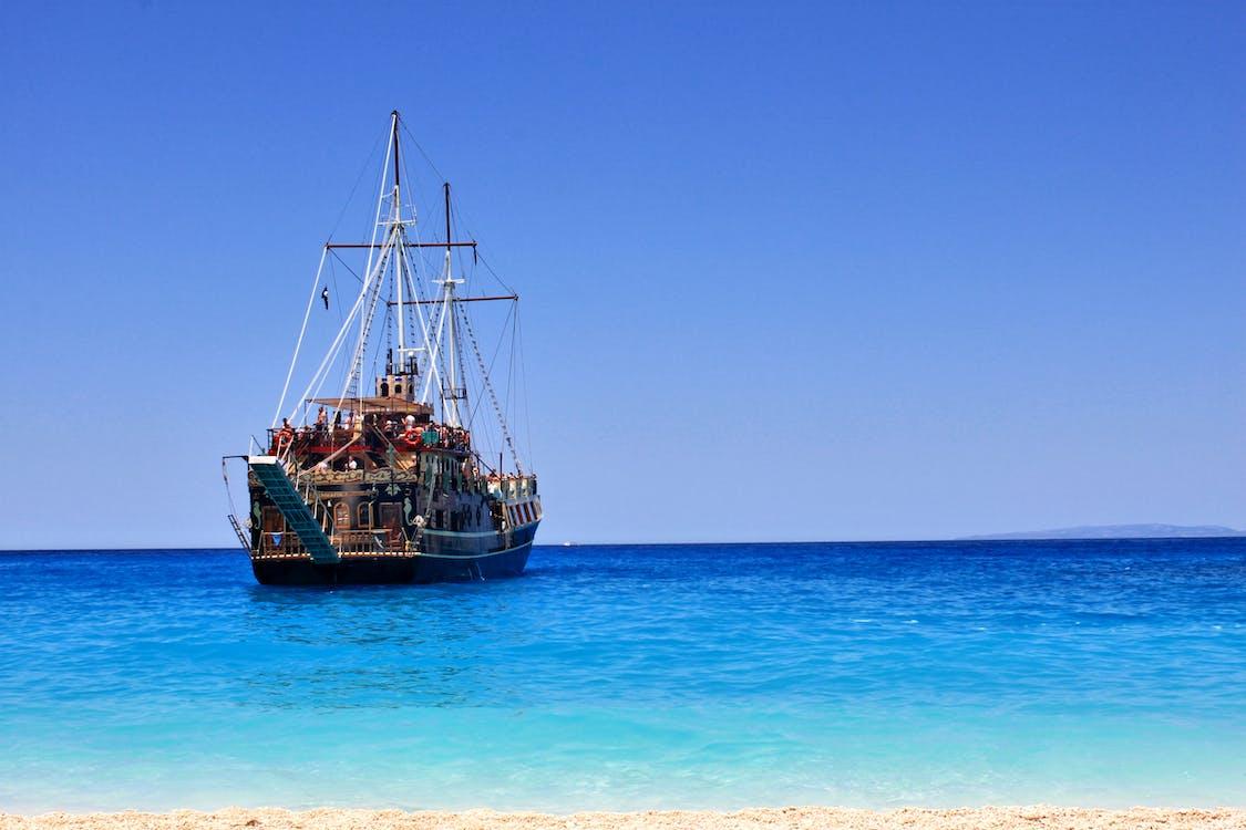 Brown Ship on Sea Under Blue Sky