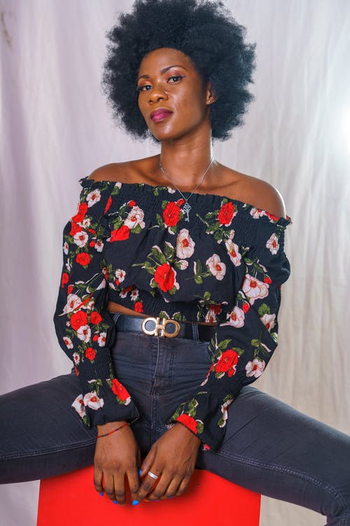 Woman with an Afro Hairstyle Wearing a Floral Off Shoulder Top