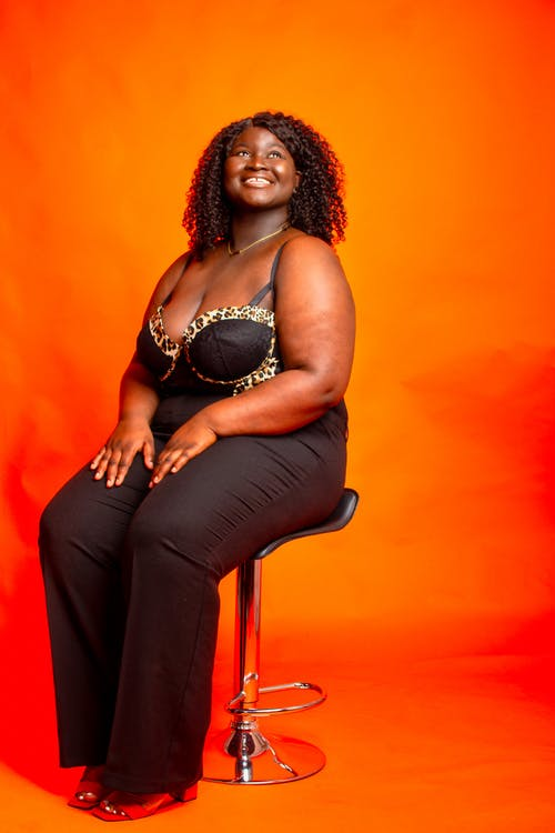 Woman in Black Pants Sitting on Orange Chair