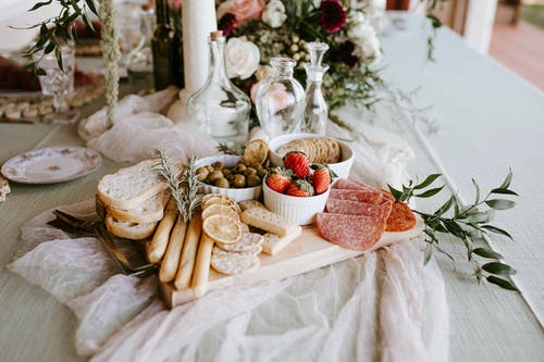 Tasty food on wooden tray on festive table
