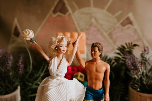 Happy couple of dolls holding hands together and raising up celebrating wedding day in hall decorated with plants