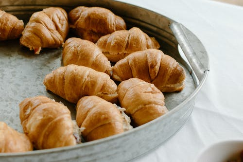 From above of baked croissants in tin tray prepared for dessert and placed on white table
