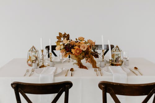 Set of dishware and cutlery placed on table decorated with candles and blooming flowers for wedding celebration