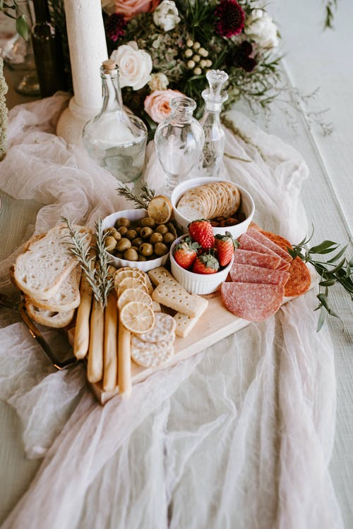 From above of wooden tray with assorted food for guests consisting of salami olives strawberries in bowls with bread and rosemary twigs on festive table