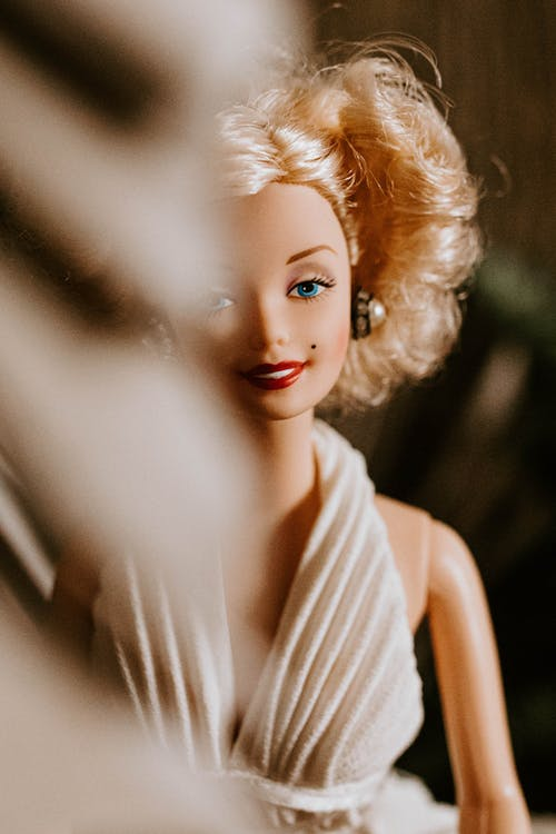 Smiling doll with blond curly hairstyle wearing elegant white decollete dress for wedding