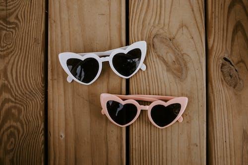 Stylish heart shaped sunglasses on wooden surface