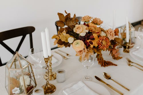 High angle of festive table decorated with bunches of blooming flowers placed near napkins candles and cutlery