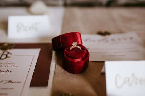 Red box with golden ring placed on table with invitation cards