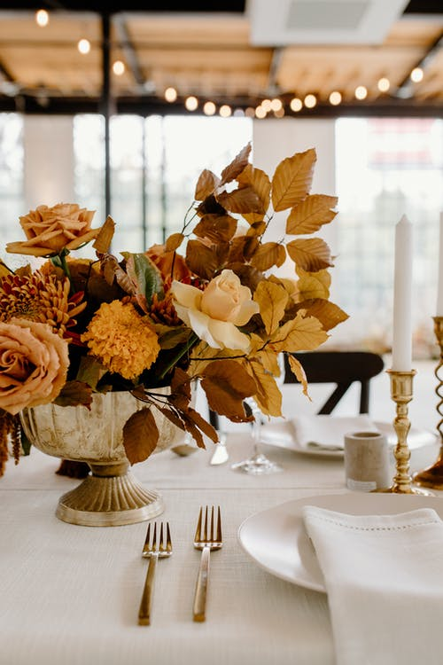 Elegant floral composition in vase placed on white table with ceramic plates and golden cutlery during festive banquet