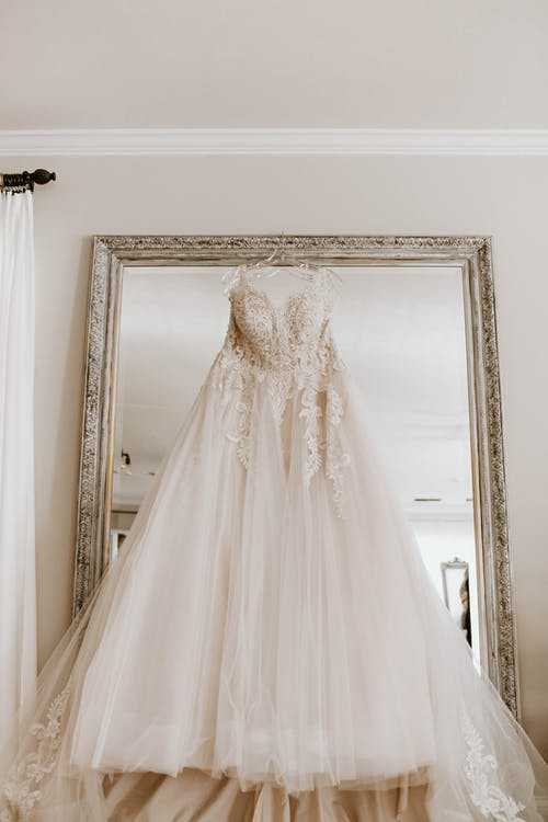 Low angle of elegant white bridal dress hanging on big framed mirror in light room before wedding ceremony