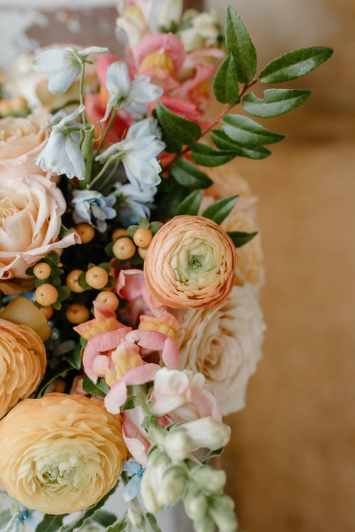 From above of fragrant bouquet with fresh peach buttercups composed with roses and green leaves in daylight
