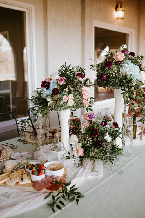 Elegant bouquets decorating banquet table with snacks and glassware