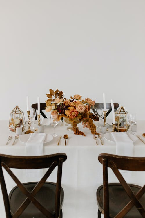 Wooden chair placed near banquet table with elegant dishware decorated with candles and floral composition against white wall