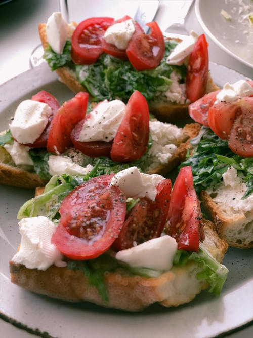 Bread with Sliced Tomato and Green Vegetable Salad on White Ceramic Plate