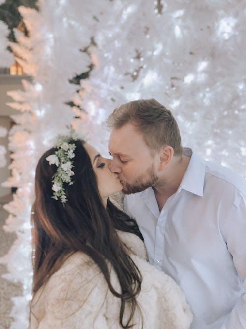 Man in White Long Sleeves Shirt Kissing Woman in White Dress