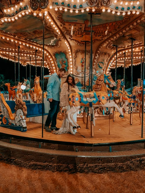 Man and Woman Riding on Carousel