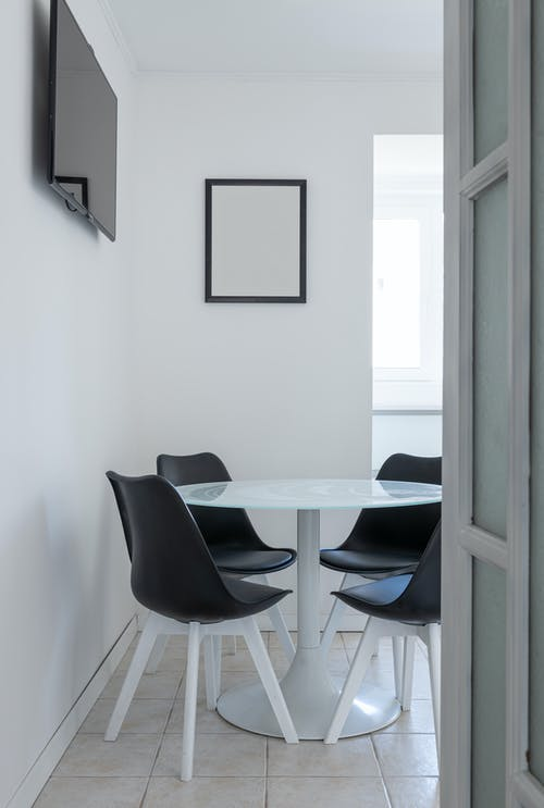 Interior of light apartment with table near chairs and tv