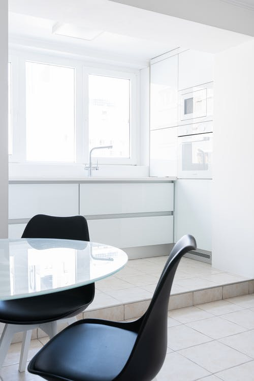 Bright modern apartment interior with glass table near chairs and windows near white counter with tap