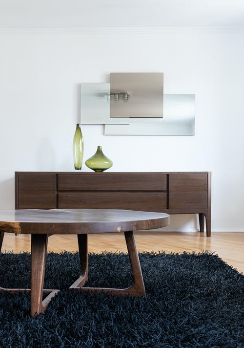 Interior of modern home with table on carpet near cabinet