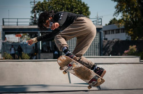 Man in Black Jacket and Brown Pants Riding Skateboard