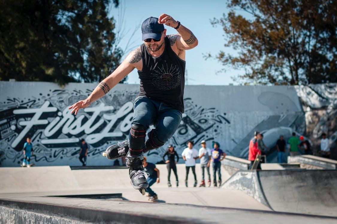 Man in Black Tank Top and Blue Denim Jeans Doing Rollerblades Stunts