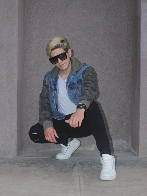 Man in Blue Denim Jacket and Black Pants Sitting on Gray Concrete Floor