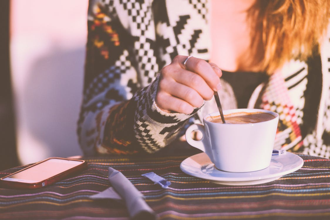 Woman Stirring Cup of Coffee on Table