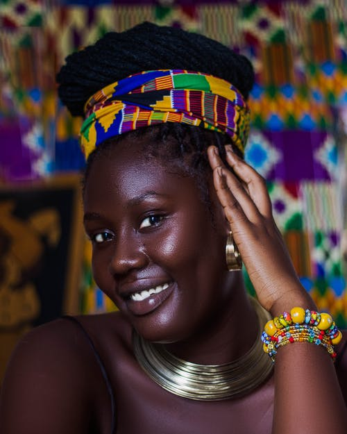 Young black female wearing colorful headdress and neck rings smiling and looking at camera