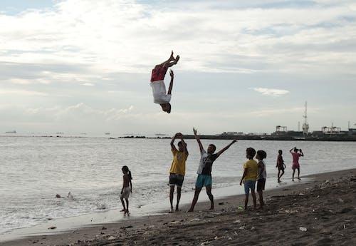 Man in White Shirt and Red Shorts Doing Backflip near Beach
