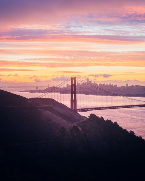 Grassy mountain near famous Golden Gate Bridge crossing river near buildings of San Francisco located on shore at sunset time against colorful sky