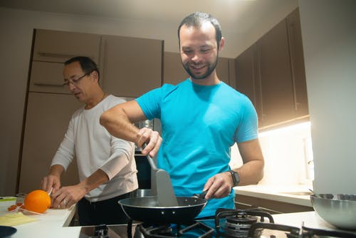 Man in Blue Crew Neck T-shirt Cooking