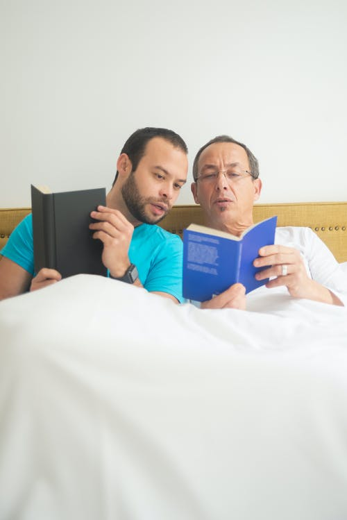 Men Reading Books while in Bed