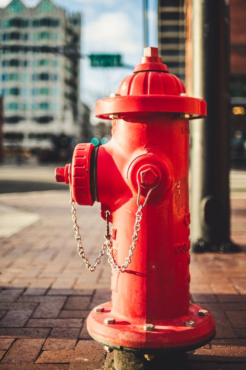 Typical red metal fire hydrant with chain located on paved street on modern city on sunny day