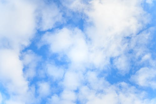 Low angle of bright blue sky with floating white fluffy cumulus clouds as abstract background