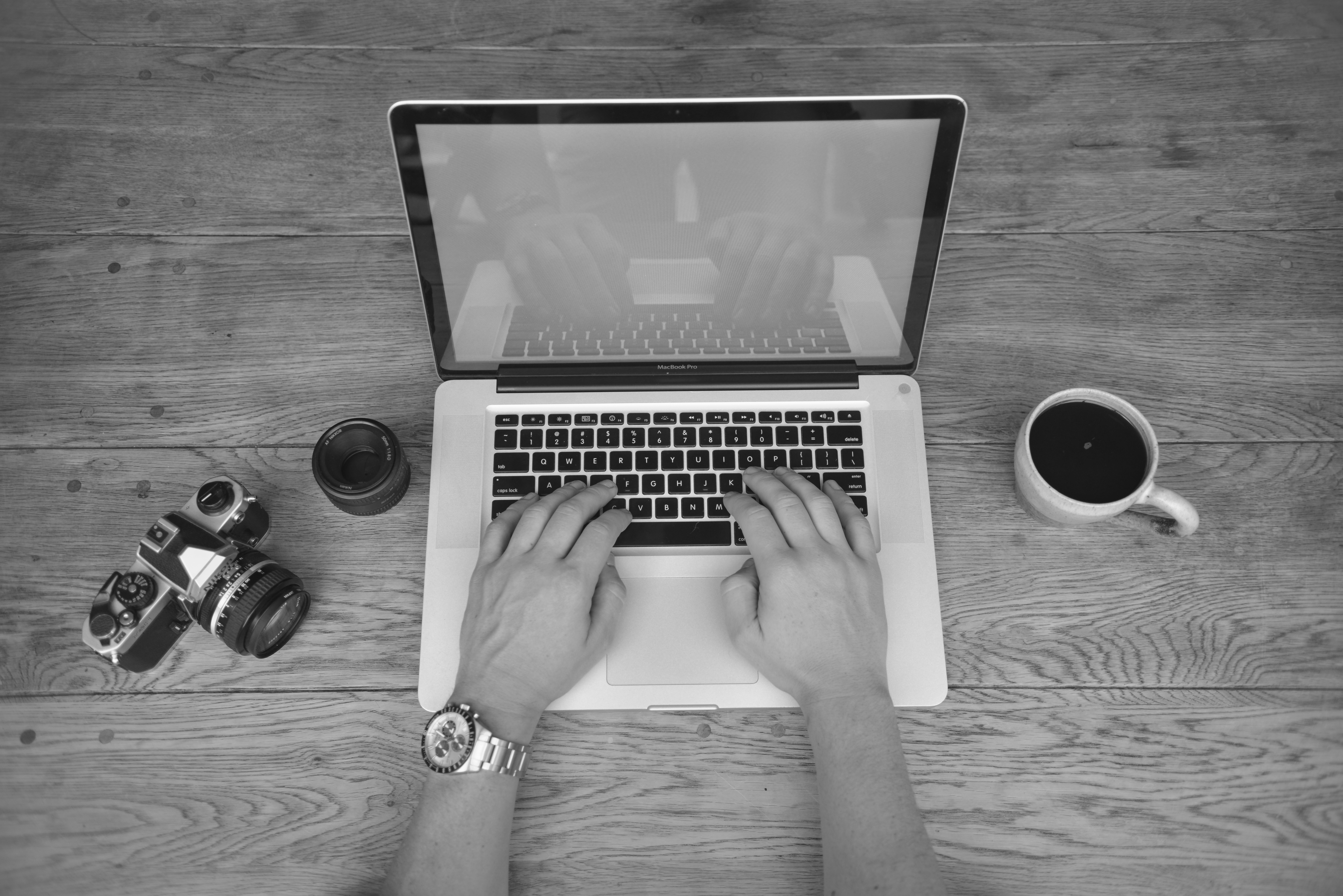 Gray Scale Photography of a Person Using Laptop