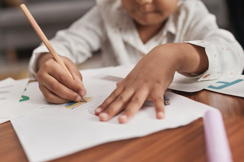 Close-Up Shot of a Kid Drawing on a Paper Using a Colored Pencil