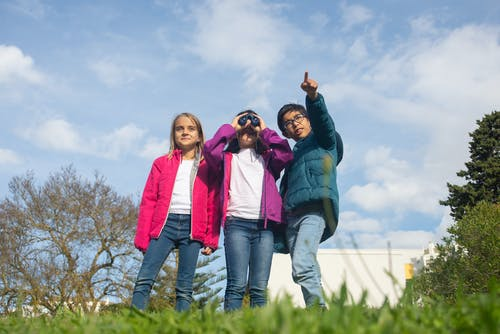 A Girl Holding a Binoculars and a Boy Pointing Where to Look At