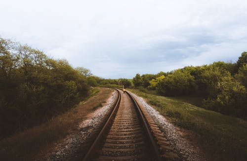 Empty narrow straight railway tracks with pebbles running through grassy woodland with lush green trees against cloudy sky in countryside