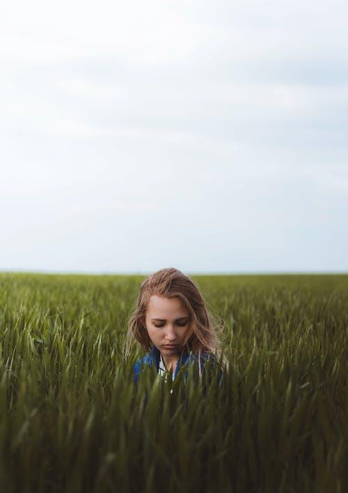 Dreamy woman sitting in grassy meadow