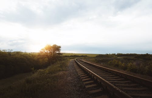 Empty narrow metal railway going along meadow with green lush bushes in nature with bright sunlight shining through tree against cloudy sky