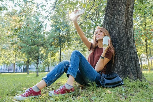 Full length of young woman in casual clothes with cup of drink sitting on green grass and using cellphone for selfie and leaning on tree in sunny day in nature