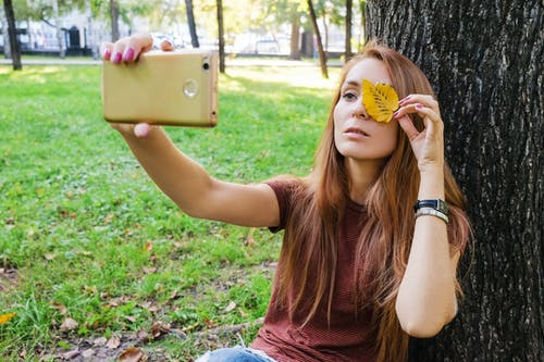 Young female in casual outfit sitting on green grass while taking selfie with phone with leaf on eye and leaning on tree in park in sunny summer day