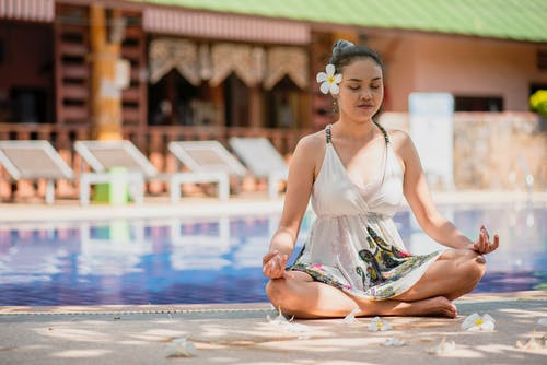 Woman in White Dress Meditating Near a Swimming Pool